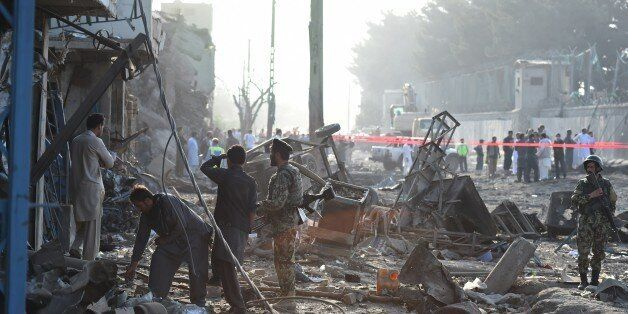 Afghan security forces inspect the site of a powerful truck bomb in Kabul on August 7, 2015. A powerful...