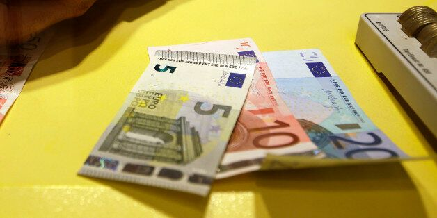 An employee counts British pounds and Euro notes at a currency exchange office in downtown Rome, Tuesday,...