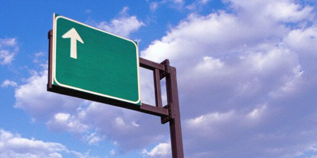 Arrow highway road sign against cloudy