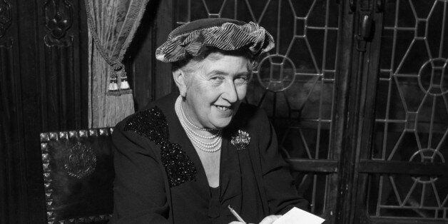 circa 1965: British mystery author Agatha Christie (1890-1976) autographing French editions of her books....
