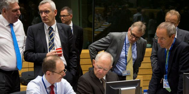 German Finance Minister Wolfgang Schaeuble, sitting center, goes over papers with members of his delegation...
