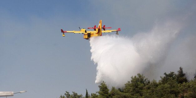 A Canadair drops water on a forest fire at the Thessaloniki Seih Sou park, which overlooks the city of...
