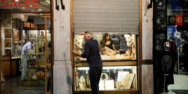 A shopkeeper closes the metal shutters outside his antique souvenir store in preparation for closing...