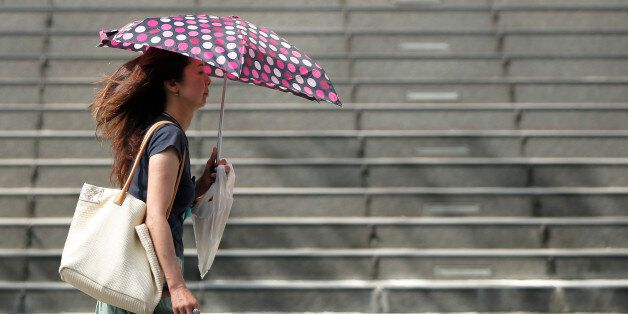 A woman uses an umbrella to shelter from the sun in Tokyo, Japan, on Monday, July 13, 2015. The Japan...