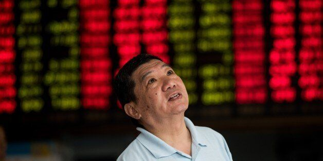 An investor monitors screens showing stock market movements at a brokerage house in Shanghai on August...