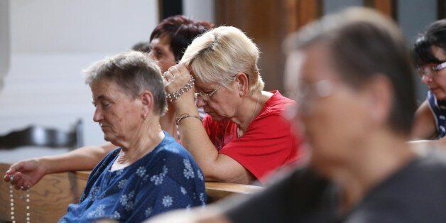 Inhabitants prays in local church in Vrpolje on August 12, 2015, after hearing in the news that Islamic...