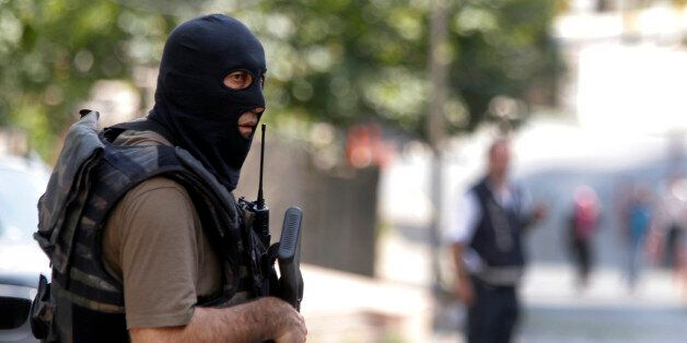 A masked Turkish police officer secures a road leading to the U. S. Consulate building in Istanbul, Monday,...