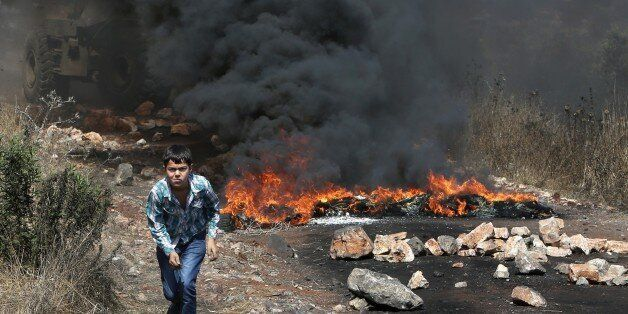 A Palestinian boy runs amid the smoke of burning tires during clashes between Palestinian protesters...