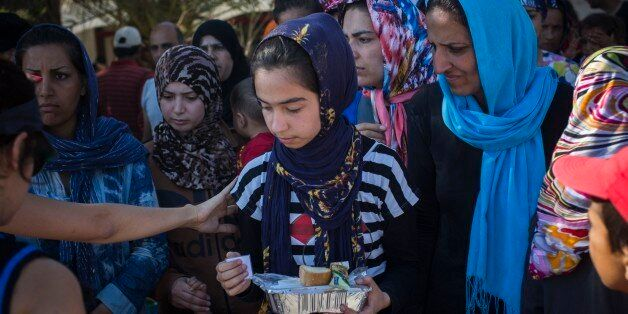 In this photo taken on Sunday, July 19, 2015 Syrian and Afghan refugees wait in line to get a meal at...