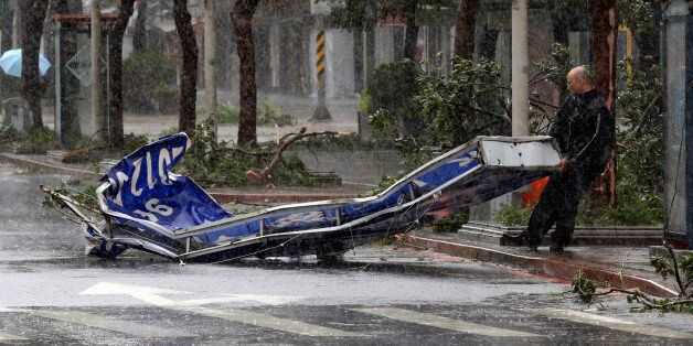 A man drags a sign brought down by strong winds from Typhoon Soudelor in Taipei, Taiwan, Saturday, Aug....
