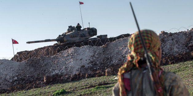 A Syrian Kurdish militia member of YPG patrols near a Turkish army tank as Turks work to build a new...