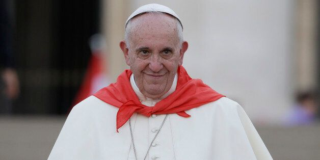 Pope Francis wears a red scarf as he leaves St. Peter's Square at the Vatican after an audience with...