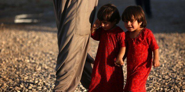 Displaced Iraqi children, who fled their homes due to attacks by the Islamic State (IS) group, walk at...