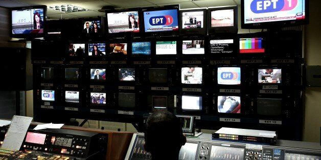 Employees of Greek state broadcaster ERT work inside the control room, during the news broadcast of the...