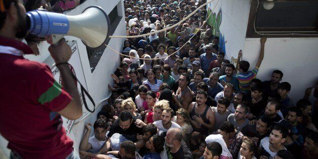 Migrants wait for a registration procedure at the stadium on the Greek island of Kos, on August 11, 2015....