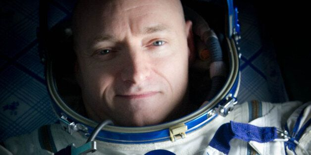 Expedition 26 Commander Scott Kelly wears a blue wrist band that has a peace symbol, a heart and the...