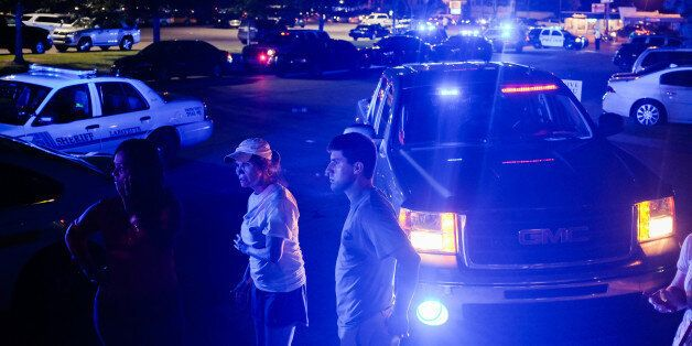 Bystanders look on as emergency personnel respond to the scene of a deadly shooting at the Grand Theatre...