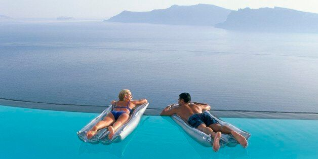 Holidaymakers on lilos in pool looking across bay, Oia, Santorini (Thira), Greek Islands, Greece, Europe
