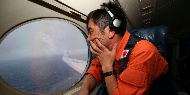 Koji Kubota of the Japan Coast Guard keeps watch through a window of their Gulfstream V aircraft while...
