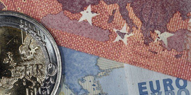 A picture taken on July 11, 2015 in Athens shows one euro coin and banknotes with the map of Europe....