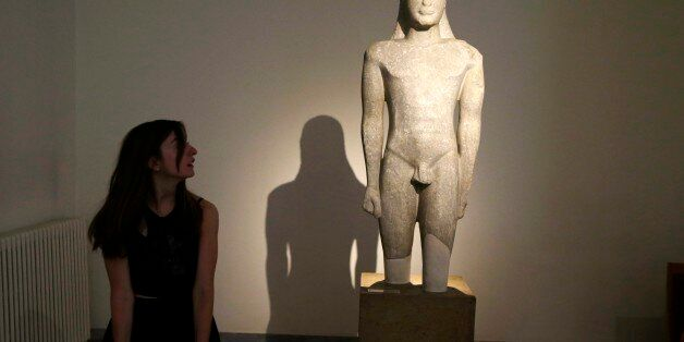 A tourist looks an ancient Greek sculpture of a kouros nude male youth, during the International Day...