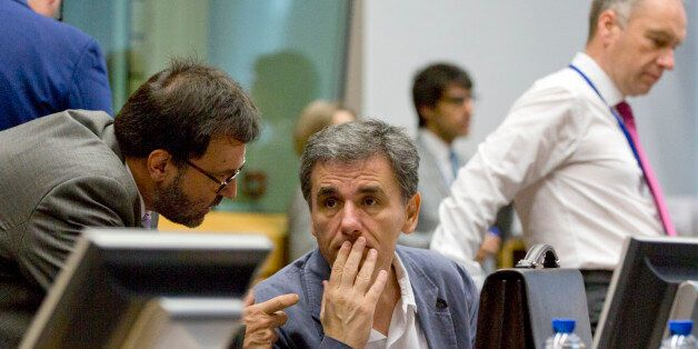 Greek Finance Minister Euclid Tsakalotos, center, speaks with a member of his delegation during a round...