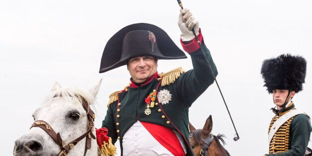 A re-enactor playing the role of the Napoleon Bonaparte rides his horse during the reconstruction