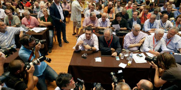 Greek Prime Minister Alexis Tsipras holds a bottle of water as he is surrounded by photographers during...
