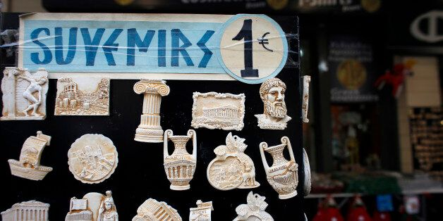 A one euro price sign sits on a display of souvenir fridge magnets for sale to tourists outside a euro...