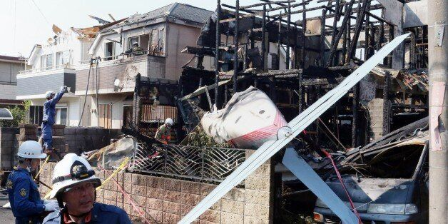 Firefighters (L) inspect a house damaged by fire caused after a light plane crashed into a residential...