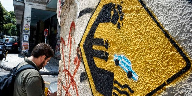 ATHENS, GREECE - JUNE 30: A man walks past anti-EU graffiti on June 30, 2015 in Athens, Greece. Greek...