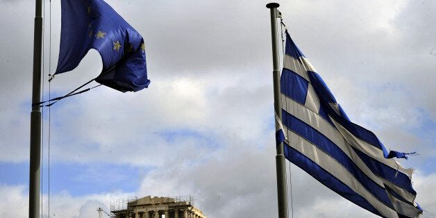Ripped EU and Greek flags flutter in Athens on February 9, 2012. The debt rescue for Greece hits an 11th-hour...