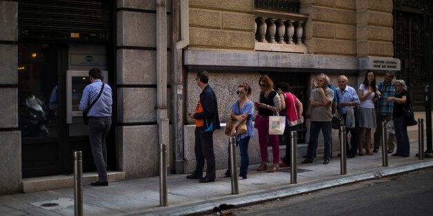 People line up to withdraw money from a bank machine in central Athens, Friday, July 3, 2015. As Greek...