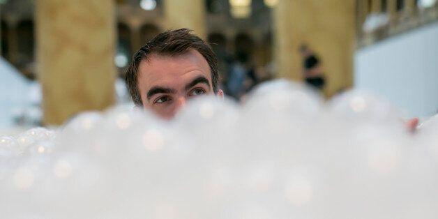 UNITED STATES - JULY 1 - Alex Mustonen, Co-founder of Snarkitecture, is seen head deep in The Beach,' an interactive architectural installation that features a 10,000 feet 'ocean' of nearly one million recyclable plastic balls during a media tour at the National Building Museum in Washington on Thursday, June 2, 2015. (Photo By Al Drago/CQ Roll Call)