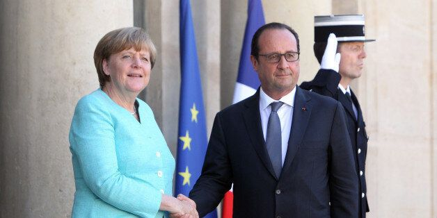 France's President Francois Hollande, right, and German chancellor Angela Merkel shake hands prior to...