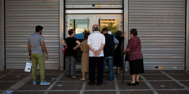 People wait to be allowed into a bank to withdraw a maximum of 120 euros ($134) for the week, in central...