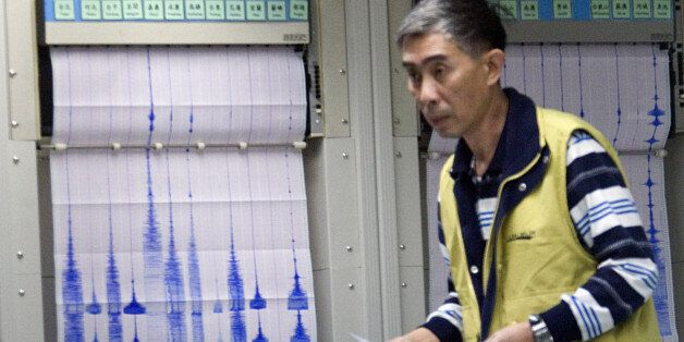 An unidentified official at Taiwan's Central Weather Bureau walks in front of seismograph readings of...