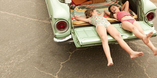 Two girls lying in estate car