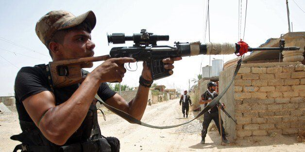 Iraqi Shiite fighters from the Popular Mobilisation force keep position during a battle against jihadists...