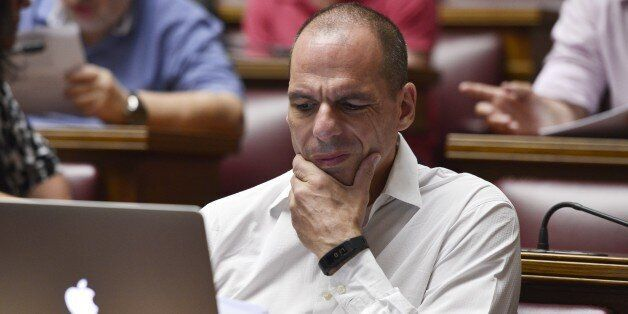 Former Greek Finance Minister Yianis Varoufakis reacts while reading a document on a laptop during a...
