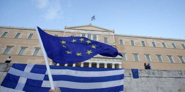 A pro-Euro demonstrator waves a European Union flag outside the Greek Parliament during a rally in Athens,...