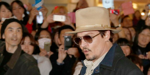 U.S. actor Johnny Depp waves to his fans upon arriving at Haneda international airport in Tokyo Monday,...