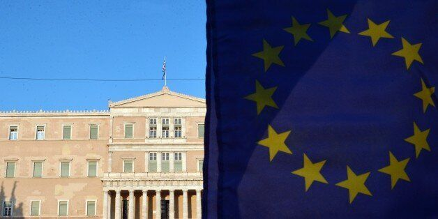 Pro-European Union protesters wave EU flags in front of the Greek parliament in Athens during a demonstration...