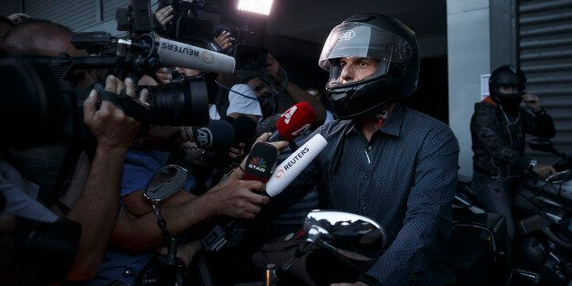 Greece's Finance Minister Yanis Varoufakis answers questions from the media as he prepares to ride his...