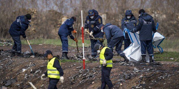 Dutch and Malaysian investigators and local authorities work, on April 16, 2015 at the MH17 plane crash...