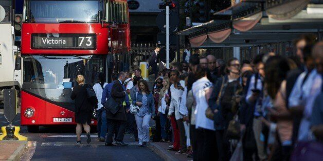 Early morning commuters form queues to board buses at Victoria station during a tube strike in London...