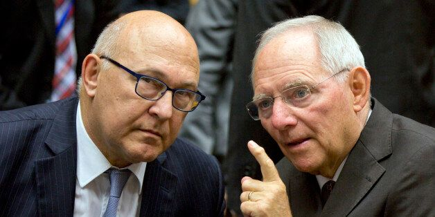 German Finance Minister Wolfgang Schaeuble, right, speaks with French Finance Minister Michel Sapin during...