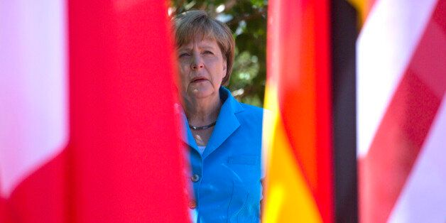 German Chancellor Angela Merkel waits near flags in the shade for G-7 leaders during arrivals for the...