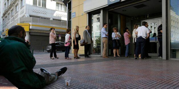 People stand in a queue to use an ATM, as a man begs for money in Athens, Wednesday, July 1, 2015. European...
