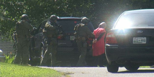 In this frame from video, law enforcement officers detain a woman as they surround a house in Hixson,...